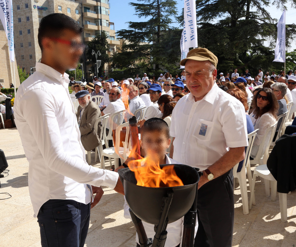 Jewish Agency Chairman Natan Sharansky kindles a memorial flame together with two members of the Nahari family (faces blurred at the family's request). Jewish teacher Moshe Ya'ish Nahari was murdered in an anti-Semitic attack in Yemen in 2008. Credit: Sasson Tiram for The Jewish Agency for Israel.