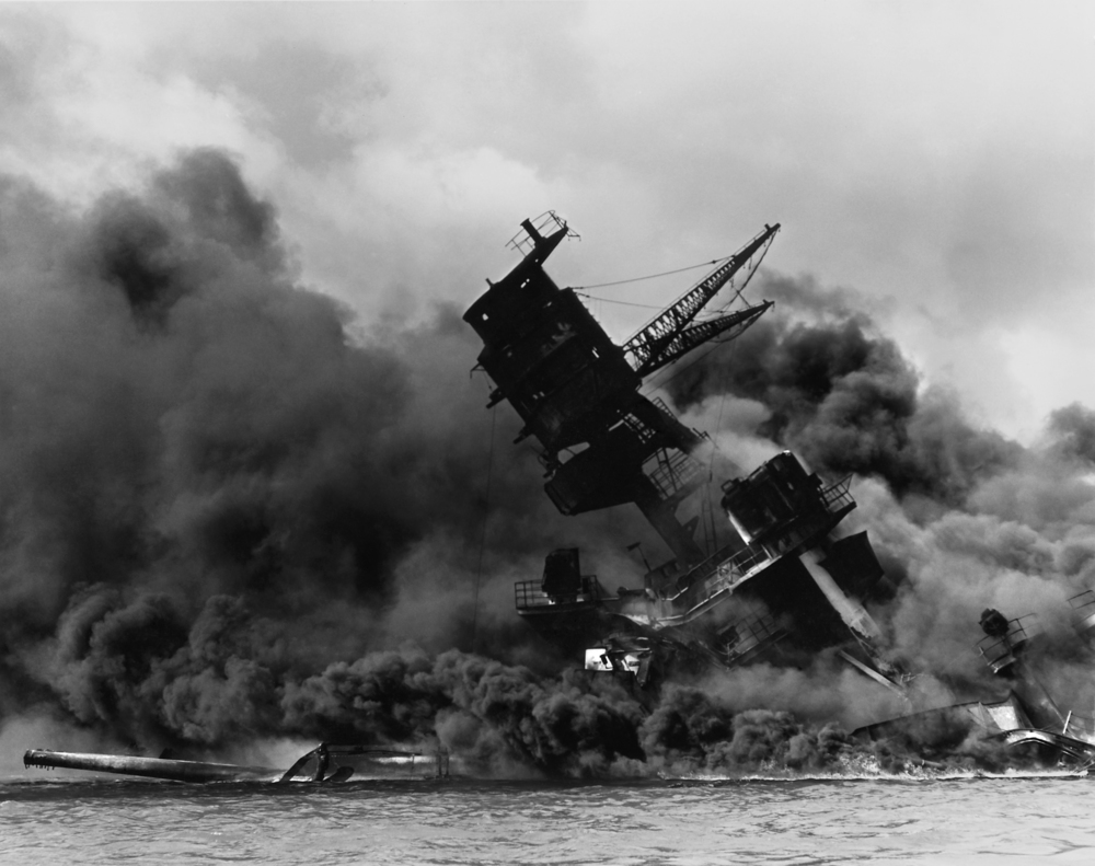 Click photo to download. Caption: In December 1941, the USS Arizona burns after being hit by a bomb in the Japanese attack on Pearl Harbor. Credit: National Archives and Records Administration via Wikimedia Commons.