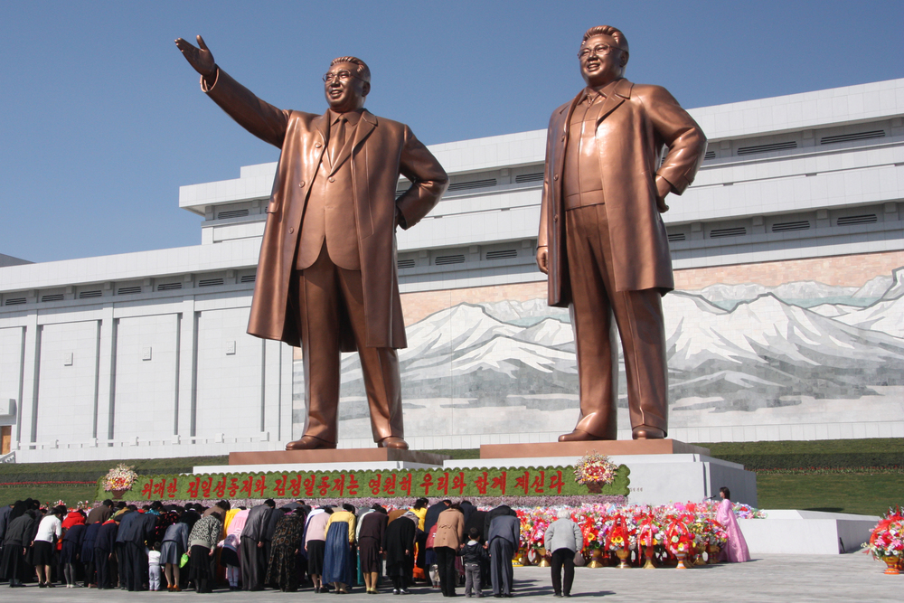Click photo to download. Caption: North Koreans bow to statues of former leaders Kim Il-sung and Kim Jong-il in the capital of Pyongyang. Credit: J.A. de Roo via Wikimedia Commons.