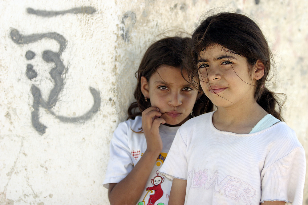 Click photo to download. Caption: Posing next to graffiti are two young residents of Aqabat Jaber, a United Nations Relief and Works Agency for Palestine Refugees in the Near East (UNRWA) camp for Palestinian refugees located near Jericho. Credit: UN Photo/Stephenie Hollyman.