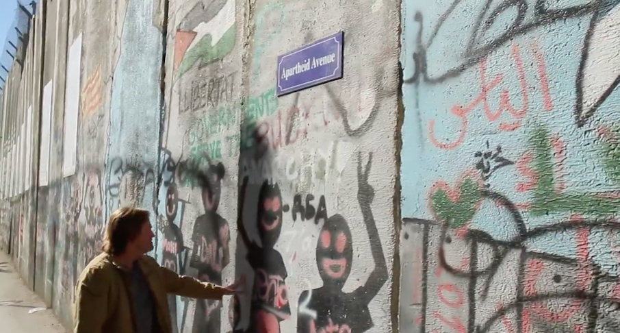 "Click photo to download. Caption: Brad Stine surveys anti-Israel graffiti in a scene from ""Hating Israel: In Search of the Truth Behind BDS."" Credit: Proclaiming Justice to the Nations."