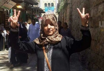 "Click photo to download. Caption: Suhair Halabi flashes ""V"" for ""Victory"" signs with both hands at the site where her son, Muhannad, carried out a deadly terrorist attack. Credit: Facebook."