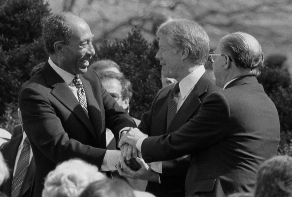 "Click photo to download. Caption: From left to right, Egyptian President Anwar Sadat, U.S. President Jimmy Carter, and Israeli Prime Minister Menachem Begin at the White House for the signing of the 1979 Egypt-Israel peace treaty. A photo of the peace treaty's signing was added to the new edition of ""The Geography of the Arab World and the History of Modern Egypt,"" a 9th-grade Egyptian textbook. Credit: Warren K. Leffler via Wikimedia Commons."
