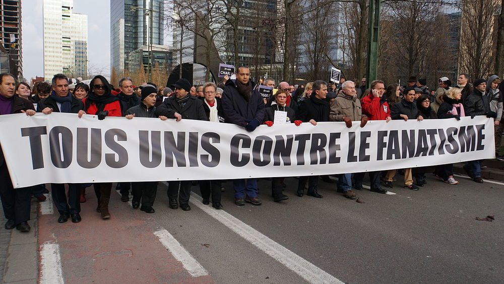 "A Brussels rally in support of the victims of the  Charlie Hebdo  shooting in January 2015. The protestors hold a sign in French that reads ""all united against fanaticism."" Credit: Miguel Discart via Wikimedia Commons."