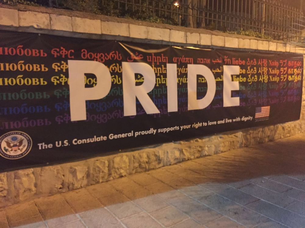 "Click photo to download. Caption: During Jerusalem's 2016 gay pride parade, a sign at the American Consulate General reads, ""The U.S. Consulate General proudly supports your right to love and live with dignity."" Credit: Eliana Rudee."