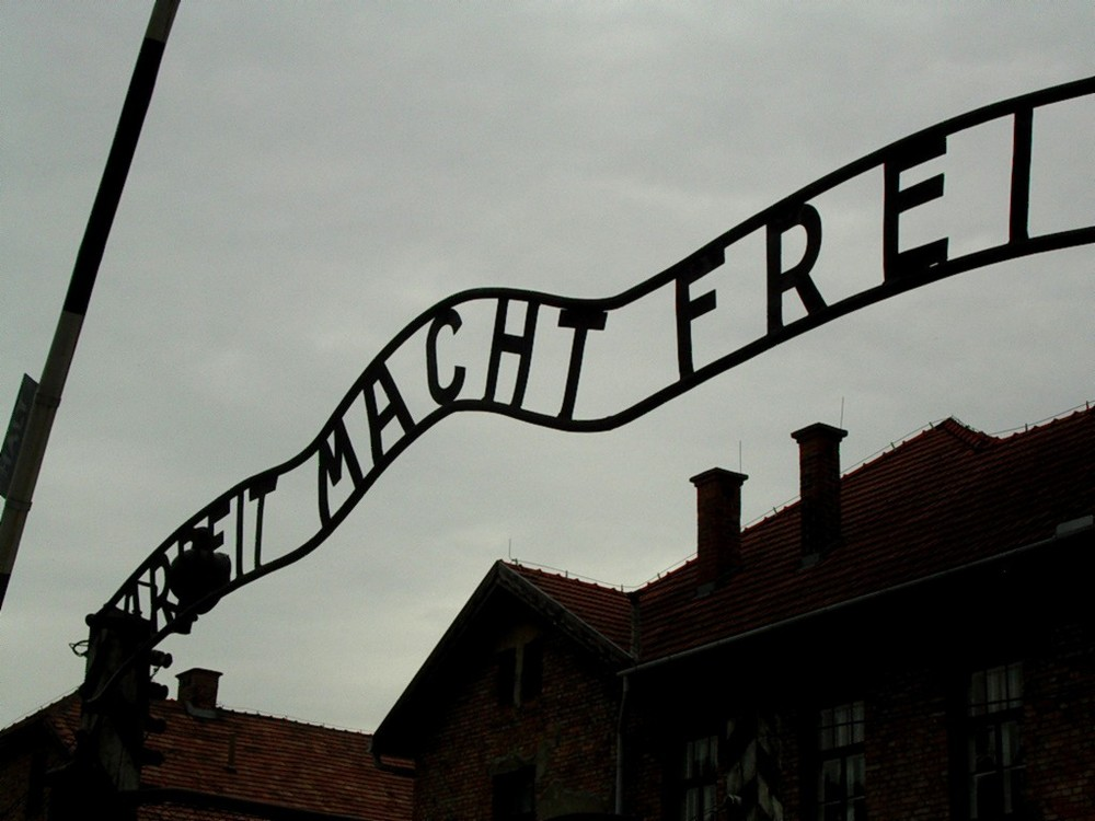 A Close-up of the main gate at Auschwitz with the inscription Arbeit Macht Frei (Work makes one free). Credit: Wikimedia Commons.