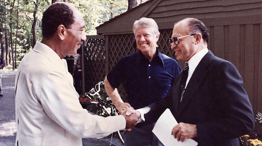 Former Egyptian President Anwar Sadat shaking hands with former Israeli Prime Minister Menachem Begin with U.S. President Jimmy Carter looking on at Camp David in 1978. Credit: Wikimedia Commons.