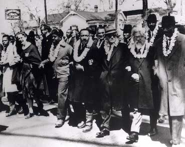 Rabbi Abraham Joshua Heschel, second from right, participating in the civil rights march from Selma to Montgomery, Alabama, on March 21, 1965. Martin Luther King, Jr. is visible behind in the second row. Credit: Wikimedia Commons.