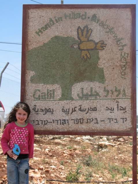 A young girl poses in front of the sign for the Galil Jewish–Arab School in northern Israel.