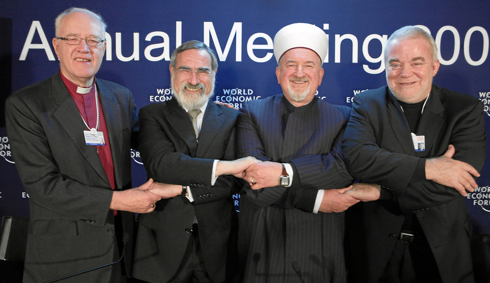 The United Kingdom's Lord Carey of Clifton, the former Archbishop of Canterbury (from left), with Jonathan Sacks, chief rabbi of the United Hebrew Congregations of the Commonwealth, and others at a press conference during the 2009 World Economic Forum in Davos, Switzerland. Credit: World Economic Forum via Flickr.