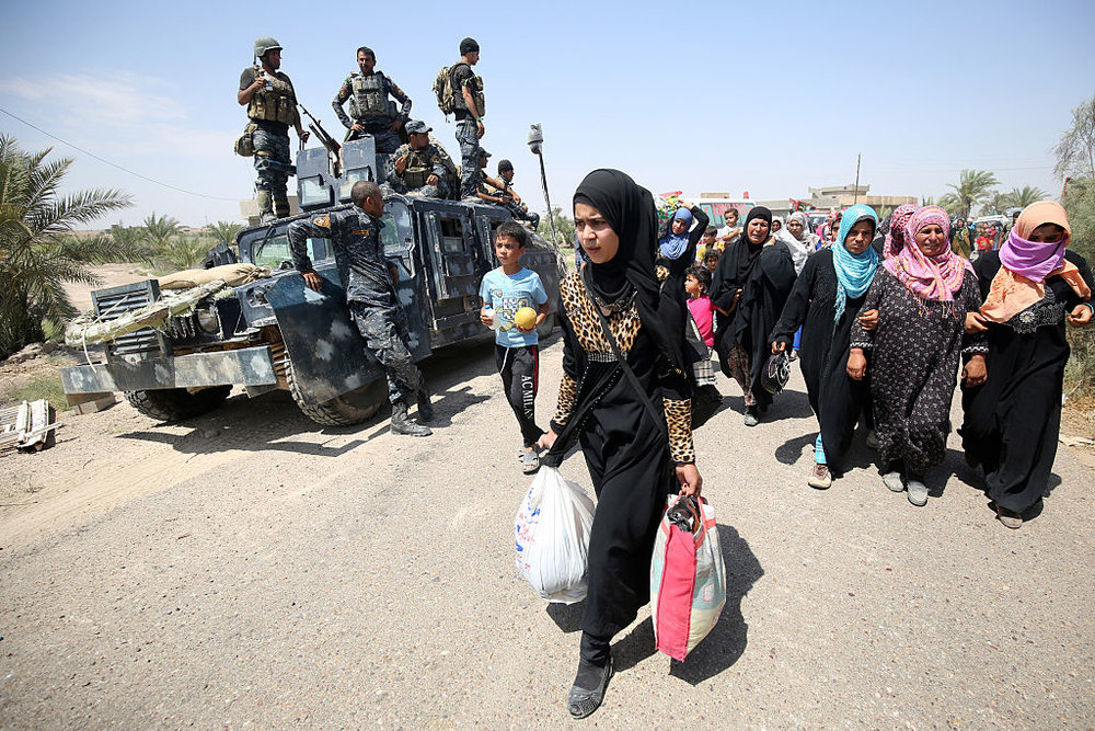Iraqi families are pictured near al-Sejar village, in Iraq's Anbar province, after fleeing the city of Fallujah, on May 27, 2016, during a major operation by pro-government forces to retake the city of Fallujah, from ISIS. Credit: AHMAD AL-RUBAYE/AFP/Getty Images