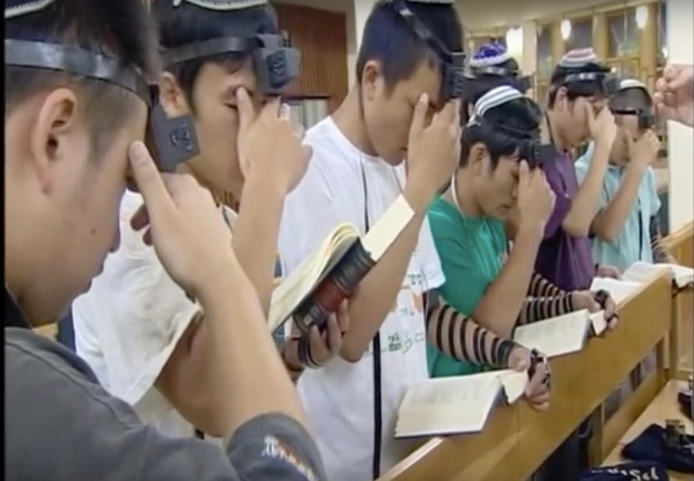 Young Chinese men from the Jewish community of Kaifeng pray with Tefillin. Credit: YouTube screenshot.