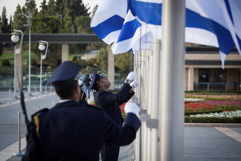 The Israeli Knesset Honor Guard lowers the Israeli flag at half-mast during a ceremony in memory of Former Israeli President Shimon Peres at the Knesset  on September 28, 2016. Credit: Hadas Parushl/Flash90.