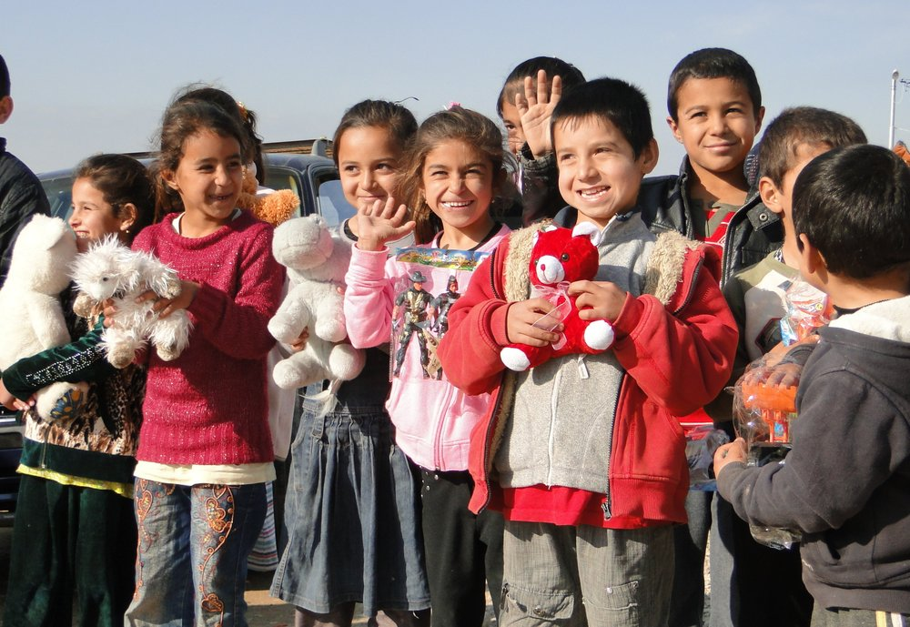 Iraqi Yazidi children receiving stuffed animals from an international aid group. Credit: Wikimedia Commons.