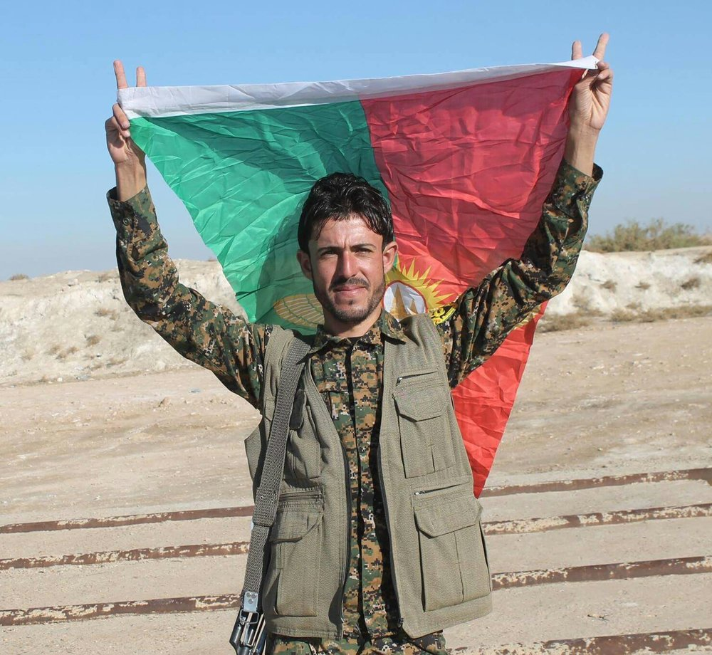 A Yazidi resistance fighter holding his people's flag. Credit: Wikimedia Commons.