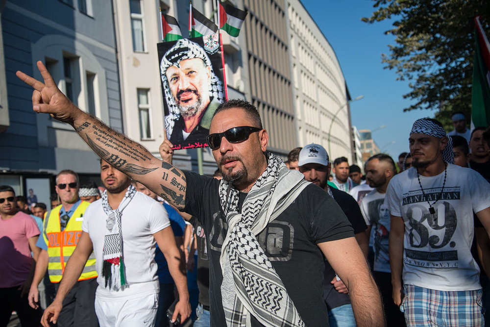 An anti-Semitic protester in Berlin with a pro-Nazi tattoo on his arm. Credit: Wikimedia Commons.
