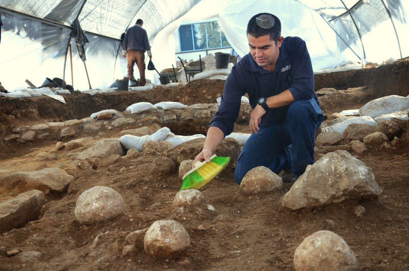 Kfir Arbib, excavation director, cleans one of the sling stones. Credit: Yoli Shwartz, courtesy of the Israel Antiquities Authority.