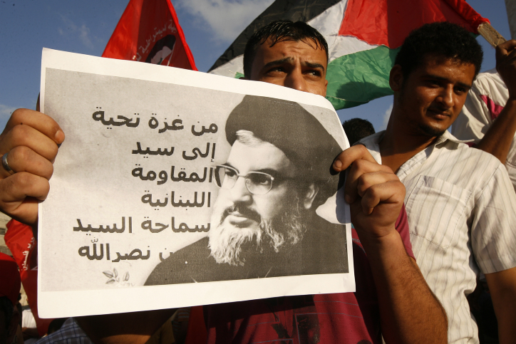 A Palestinian protester from the Popular Front for the Liberation of Palestine (PFLP) holds a picture Hezbollah leader Sheikh Hasan Nasrallah during a demonstration in Rafah, in the southern Gaza Strip, on Sept. 3, 2014.Credit: Abed Rahim Khatib/Flash 90.