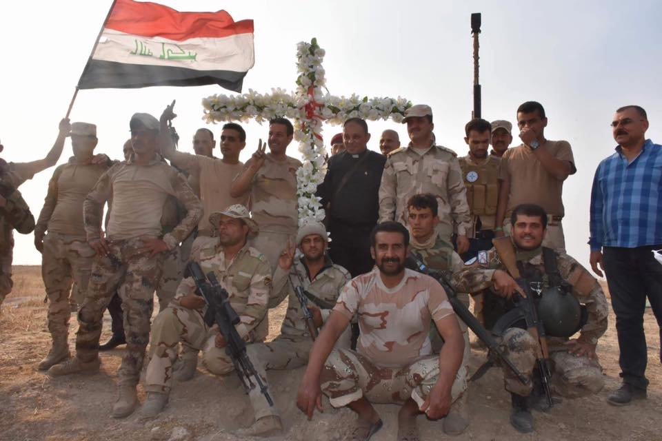 Soldiers from the Nineveh Plains Protection Units pose with a priest and a cross along with the Iraqi flag. Credit: Nineveh Plains Protection Units.