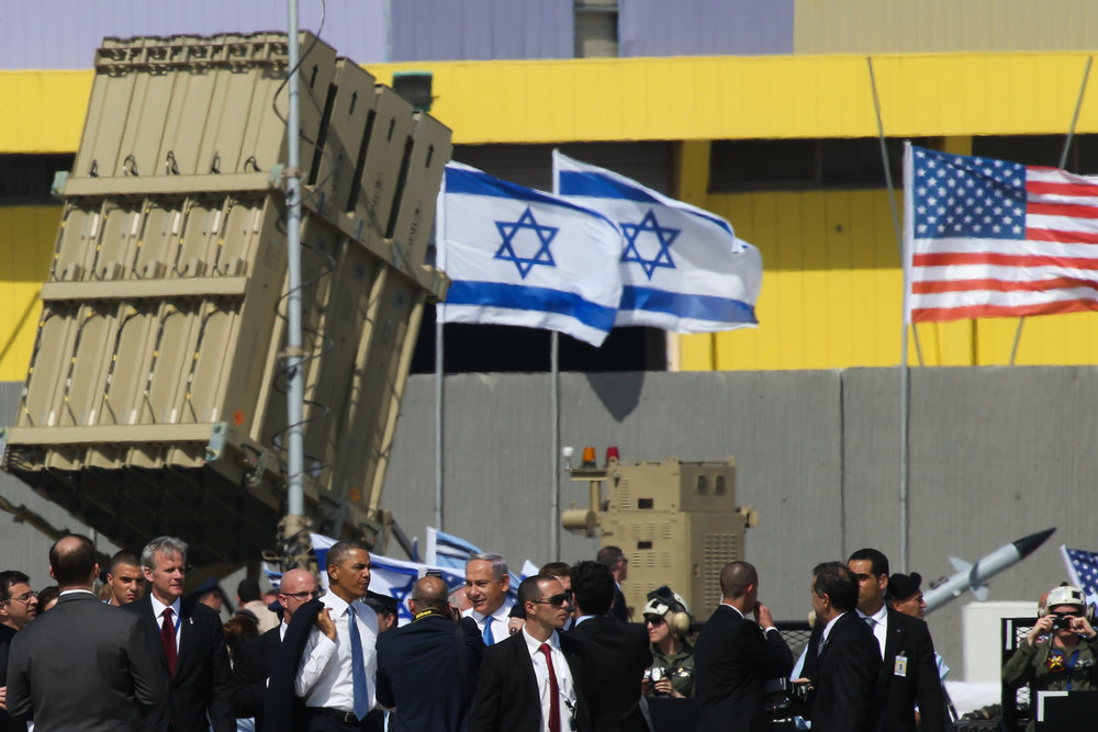 In March 2013 near Tel Aviv, American and Israeli officials—including President Barack Obama and Prime Minister Benjamin Netanyahu—are pictured next to a battery of the Iron Dome, Israel's U.S.-funded missile defense system. Credit: Nati Shohat/Flash90.