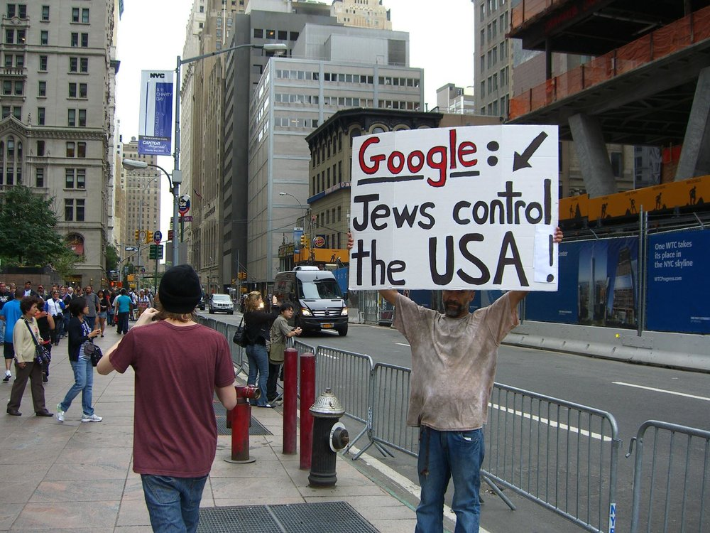 A man holds a sign promoting an anti-Semitic conspiracy theory across the street from the former World Trade Center site on Sept. 11, 2011, the 10th anniversary of the 9/11 attacks. Credit: Luigi Novi via Wikimedia Commons.