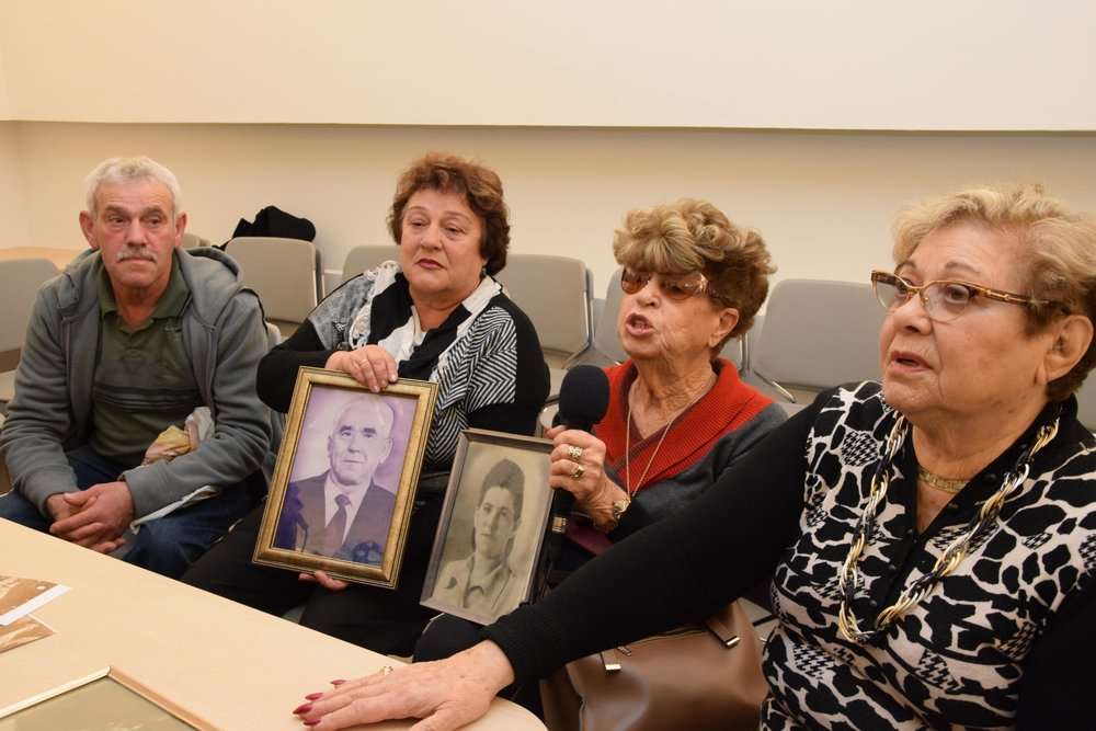 From left to right, relatives Gennadi Band, Fania Bilkay, Henia Borenstein Moskowitz and Ryvka Borenstein Patchnik meet at the Yad Vashem Holocaust remembrance center in Jerusalem Dec. 13, the first day they were ever in the same room together. Fania and Henia are holding pictures of siblings Nisan Band and Jenta Band Borenstein, who both survived the Holocaust but are no longer alive. Credit: Yad Vashem/Karina Pasternak.