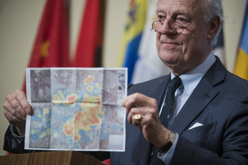 Staffan de Mistura, the United Nations special envoy for Syria, holds up a photo of Aleppo while briefing journalists following a UN Security Council emergency meeting on the situation in Syria Dec. 13, 2016. Credit: UN Photo/Amanda Voisard.