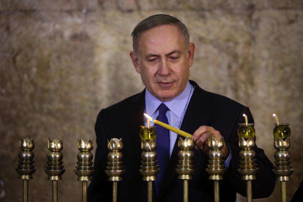 Israeli Prime Minister Benjamin Netanyahu lights a Hanukkah menorah Dec. 25 at the Western Wall in Jerusalem. Credit: Marc Israel Sellem/POOL.
