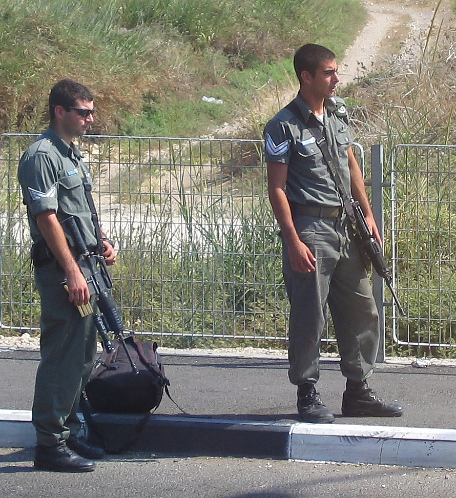 Israeli soldiers attempt to hitchhike at an intersection of two major highways. Credit: Patrick Brennan via Wikimedia Commons.