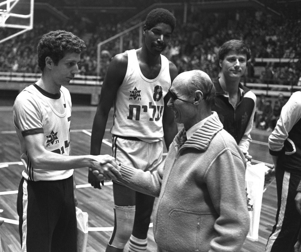 Iconic Israel defense leader Moshe Dayan, pictured here with Maccabi Tel Aviv players, was one of the officials who worked to elevate the sport of basketball in Israeli society. Credit: On The Map.