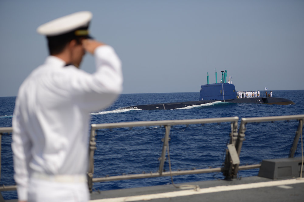 An Israeli Navy member gives a salute and looks on in September 2014 while a memorial ceremony is held at sea—from the navy's INS Tanin submarine—for the personnel of the INS Dakar, which sank off the coast of Haifa in 1968. Credit: Gadi Yampel/IDF Spokesperson/Flash90.