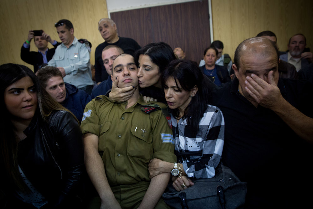 Israeli soldier Sgt. Elor Azaria, who shot dead an immobilized Palestinian terrorist in Hebron last March, is surrounded by family and friends as he awaits to hear his verdict in a courtroom at the Kirya military base in Tel Aviv Jan. 4, 2017. Azaria was convicted of manslaughter. Credit: Miriam Alster/Flash90.