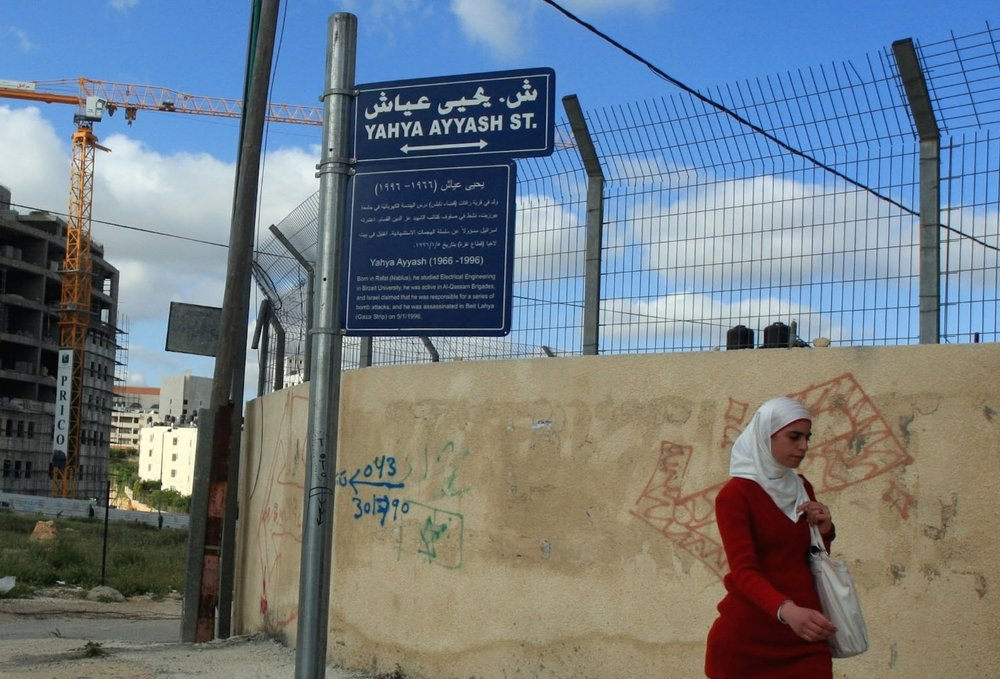 In the de facto Palestinian Authority capital of Ramallah in the West Bank, a Palestinian woman walks past a street sign bearing the name of Yahya Ayyash, the Hamas terror group's former chief bomb-maker. Credit: Issam Rimawi/Flash90.