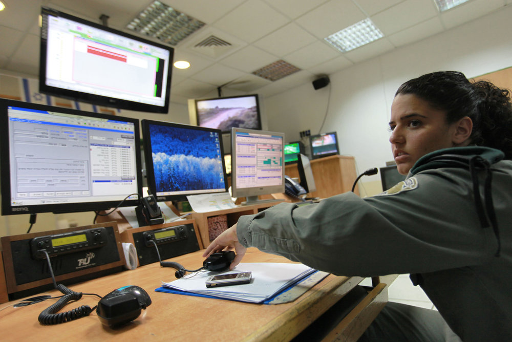 An Israeli Border Police officer sits in front of computer monitors and radio transmitters in a control and communications room in Jerusalem. Credit: Nati Shohat/Flash90.
