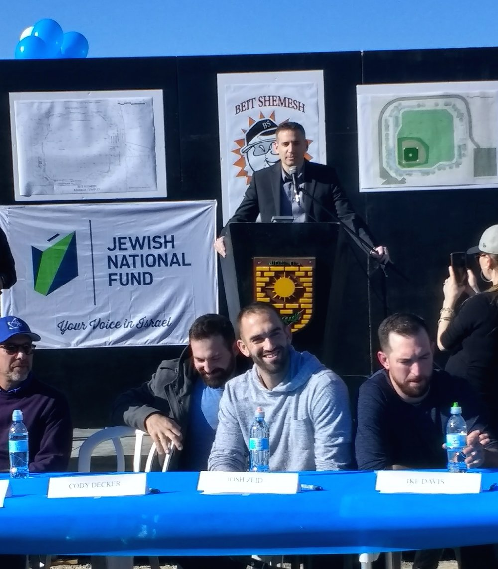From left to right at the table, during the Jan. 6 groundbreaking for Israel's new Beit Shemesh Baseball Complex: Israel Association of Baseball President Peter Kurz; Cody Decker of the Milwaukee Brewers organization; Josh Zeid, formerly of the Houston Astros; and Ike Davis, formerly of the New York Mets. At the podium is Eric Michaelson, Jewish National Fund's chief Israel officer. Credit: Yocheved T. Kolchin.