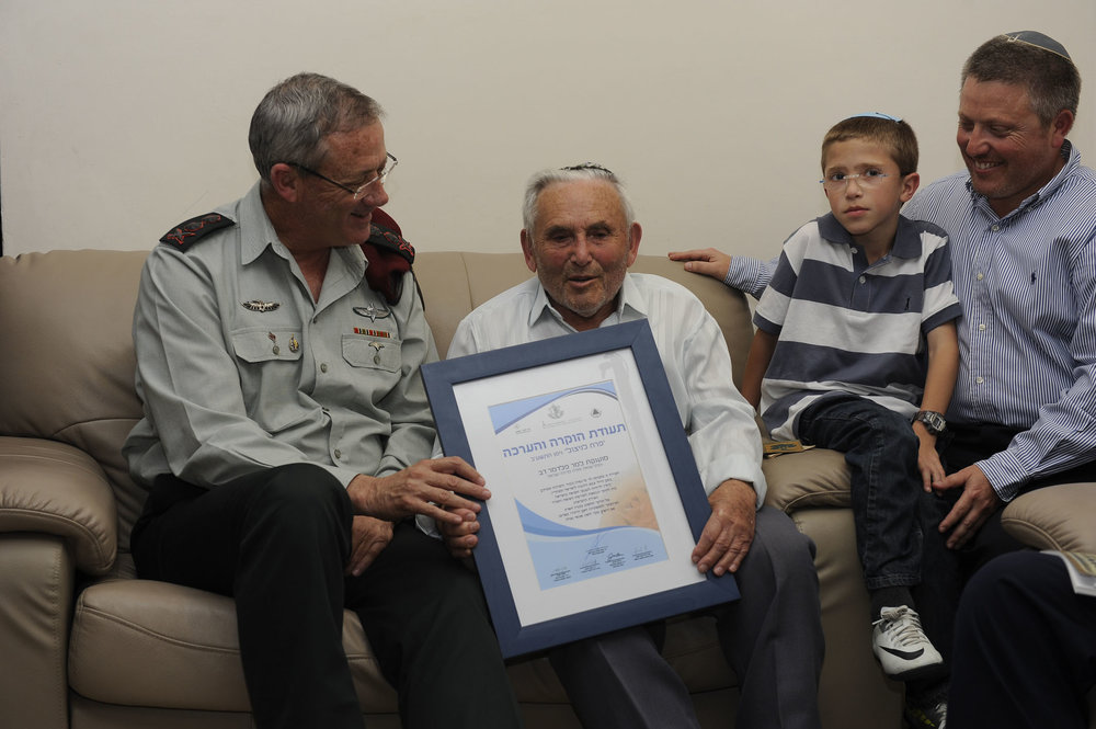 """Israel Defense Forces (IDF) soldiers, including former IDF Chief of the General Staff Lt. Gen. Benny Gantz (left), visit with a Holocaust survivor (holding as part of the """"Flower for a Survivor"""" project, in which soldiers visit Holocaust survivors in honor of Israel's annual Holocaust Remembrance Day. Credit: IDF."""