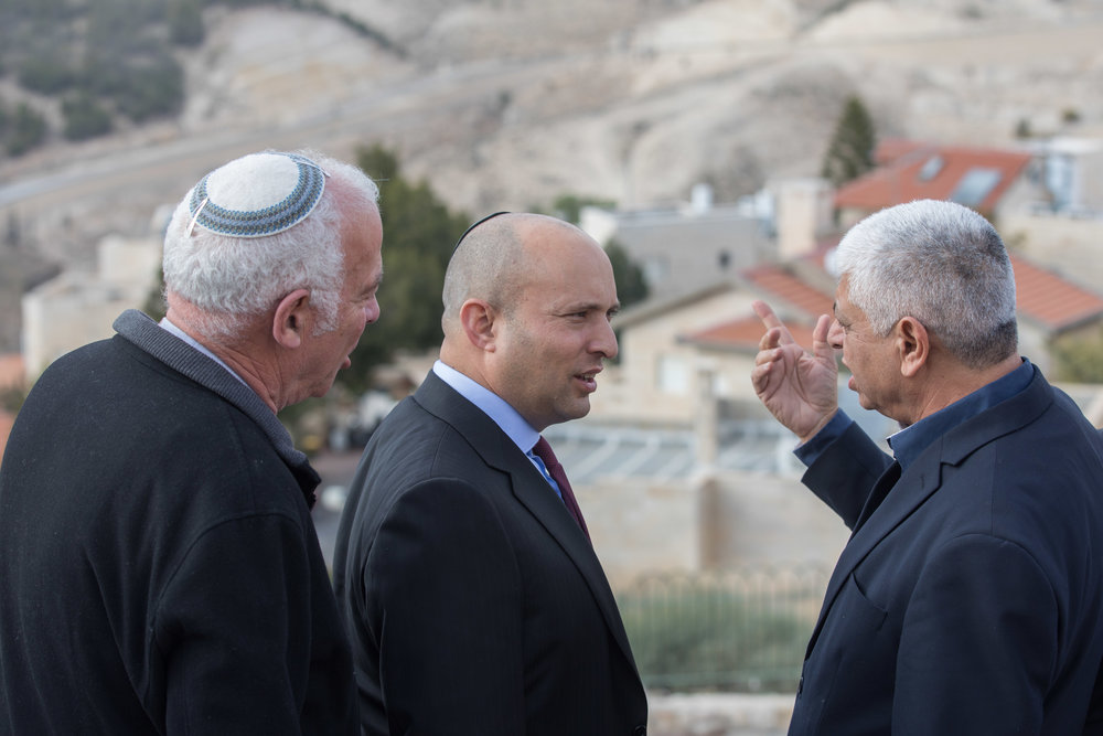 Jewish Home party leader Naftali Bennett (center) speaks with Ma'ale Adumim Mayor Benny Kasriel (right) before the start of a special Jewish Home faction meeting in the Israeli settlement of Ma'ale Adumin in the West Bank Jan. 2. Bennett has advocated for a Knesset bill to be introduced after President-elect Donald Trump takes office Jan. 20 calling for Israel's annexation of Ma'ale Adumim. Credit: Yonatan Sindel/Flash90.