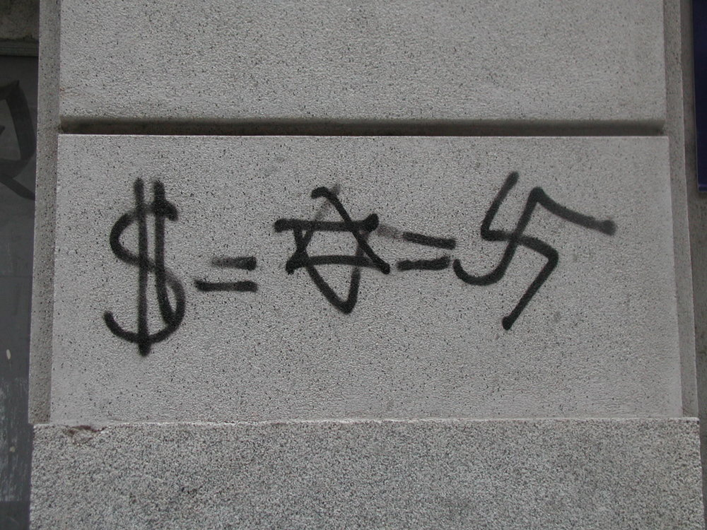 Graffiti in Madrid, Spain, illustrating the anti-Semitic conspiracy theory of Jewish control over money. Credit: Wikimedia Commons.