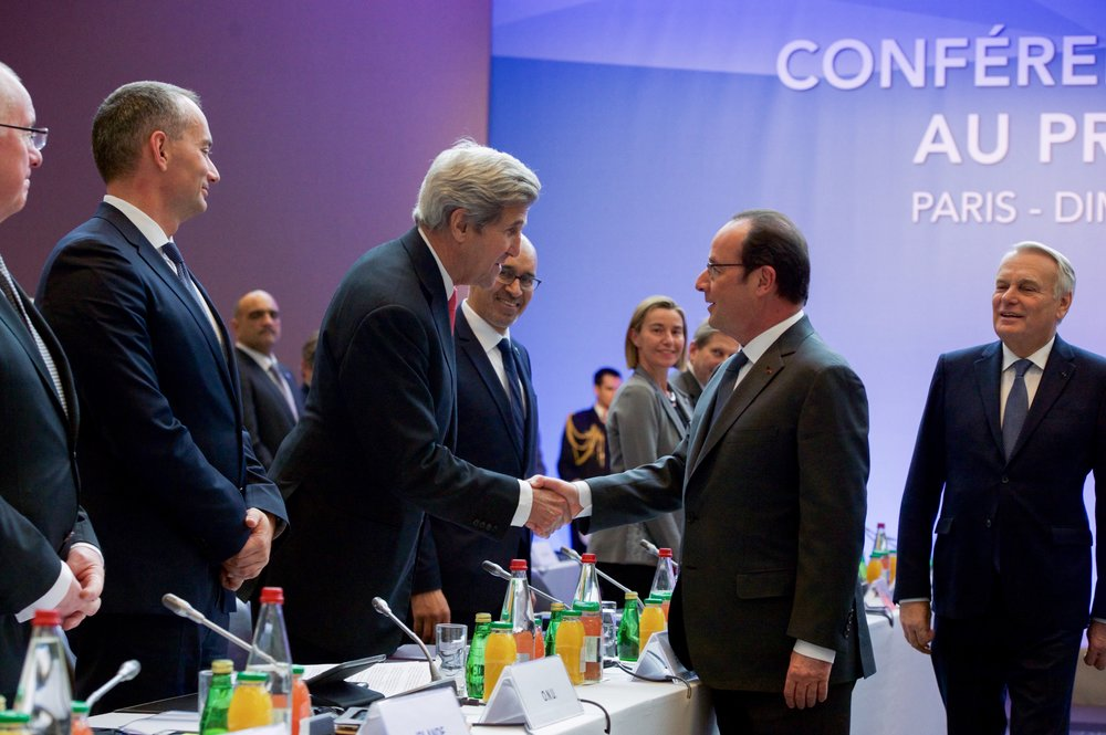 U.S. Secretary of State John Kerry and French President Francois Hollande, pictured in center, shake hands at the Jan. 15 conference on Mideast peace in Paris. Credit: U.S. State Department.