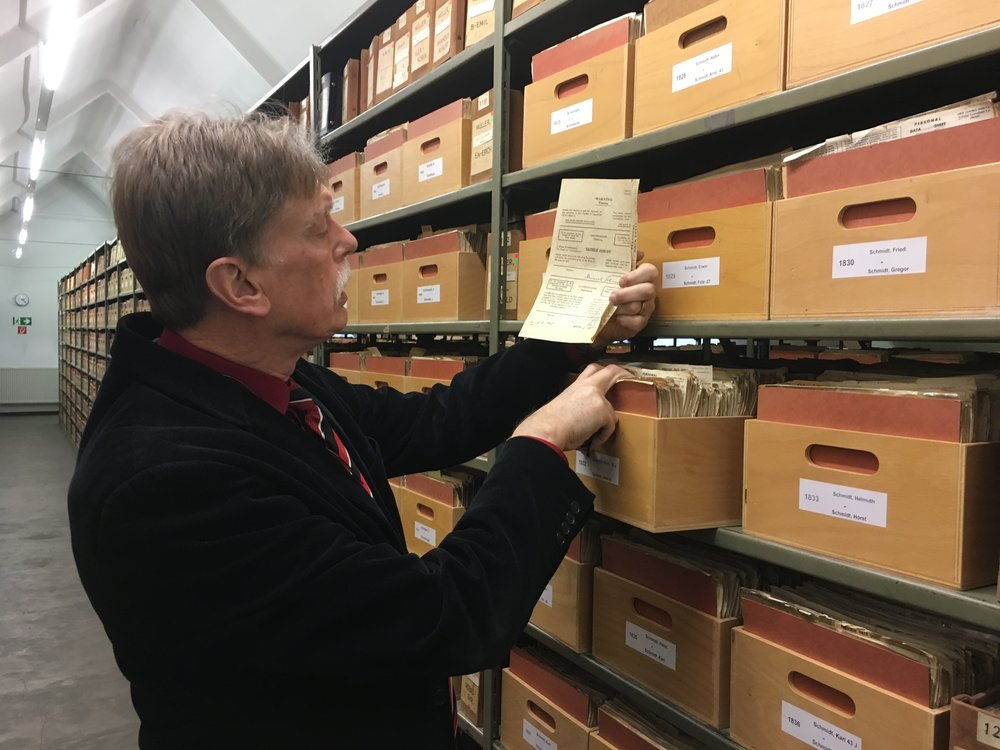 Hans-Hermann Söchtig, director of the German government agency Deutsche Dienststelle (WASt), examines a folder in the WASt archives, which help descendants of Nazi soldiers learn more about their father or grandfather's wartime service. Credit: Orit Arfa.