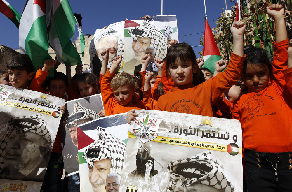 Palestinian children hold posters with the picture of former Palestinian leader Yasser Arafat and current Palestinian Authority President Mahmoud Abbas during a rally in Hebron marking the 12th anniversary of Arafat's death Nov. 10, 2016. Credit: Wisam Hashlamoun/Flash90.