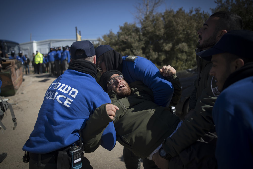 Israeli police forces carry out the evacuation of Amona as a resident resists the court-ordered process Feb. 2. Credit: Yonatan Sindel/Flash90.