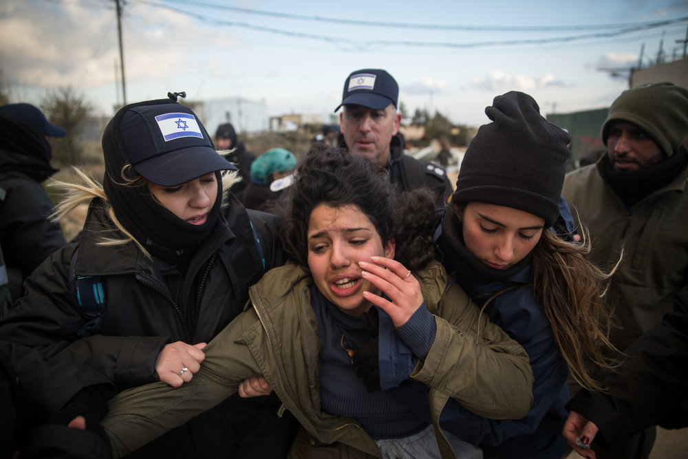 A young woman is arrested and carried by police during the evacuation of the Amona outpost Feb. 1, 2017. Credit: Hadas Parush/Flash90.