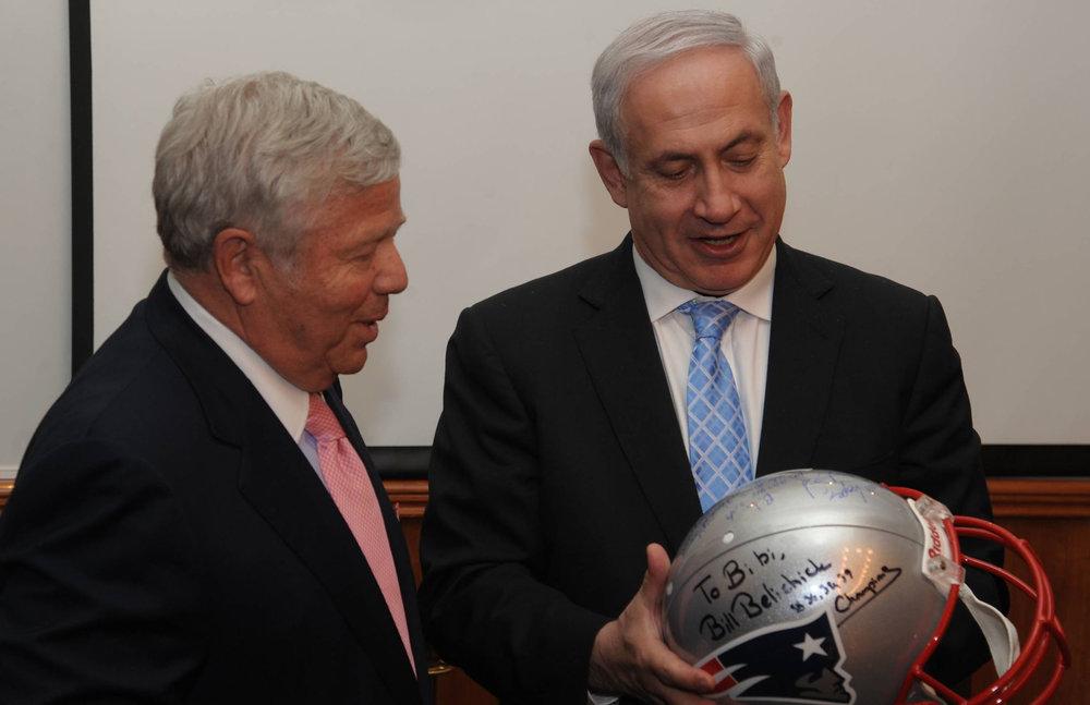 New England Patriots owner Robert Kraft (left) presents Israeli Prime Minister Benjamin Netanyahu with a football helmet signed by members of the Patriots. Credit: Amos Ben Gershom/GPO.