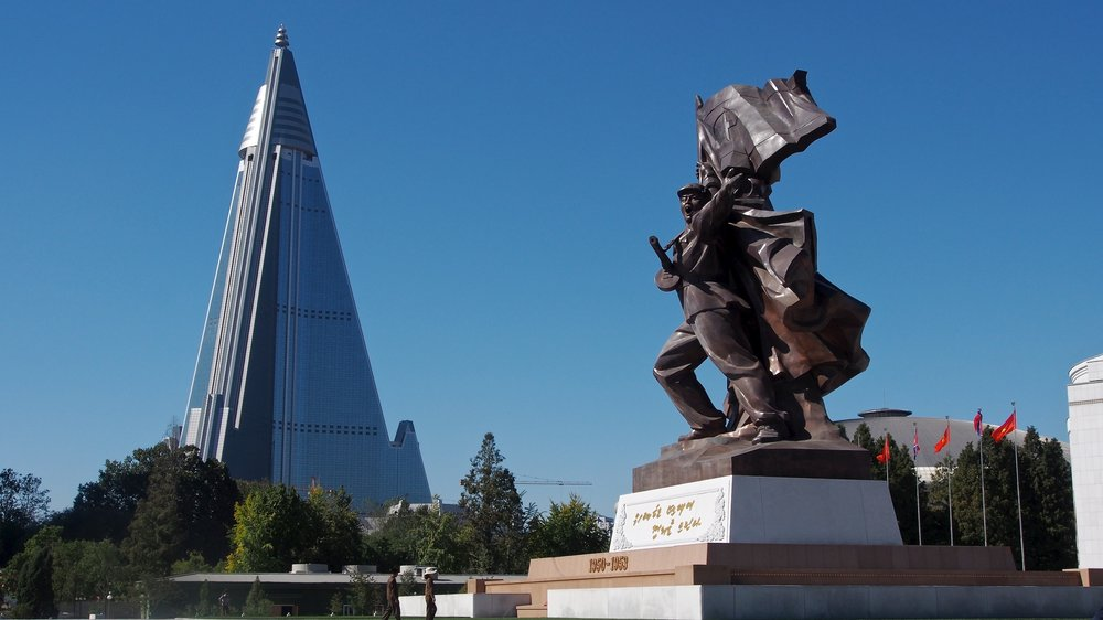 The Ryugyong Hotel and part of the Monument to the Victorious Fatherland Liberation War in Pyongyang, North Korea. Credit: Clay Gilliland via Wikimedia Commons.