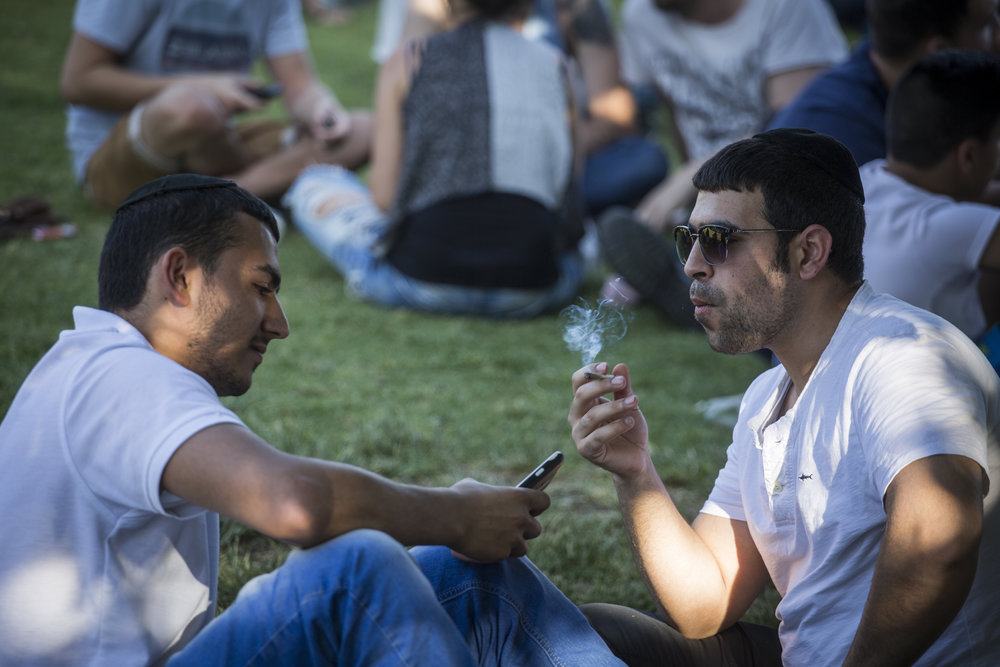 """Israelis gather at the Rose Garden in front of the Knesset legislature to smoke marijuana April 20, 2016, marking the international """"4/20"""" marijuana celebration day and advocating for Israel to legalize the drug. Credit: Hadas Parush/Flash90."""