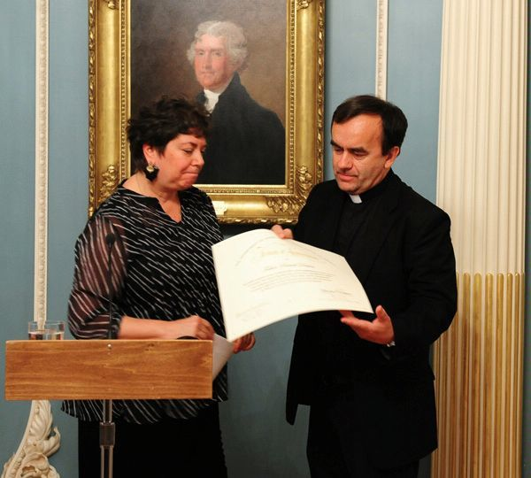 Former U.S. Special Envoy to Monitor and Combat Anti-Semitism Hannah Rosenthal (left) recognizes the work of Father Patrick Desbois, president of the Yahad-In Unum Association of France, with a Tribute of Appreciation certificate in May 2011. Credit: U.S. State Department.