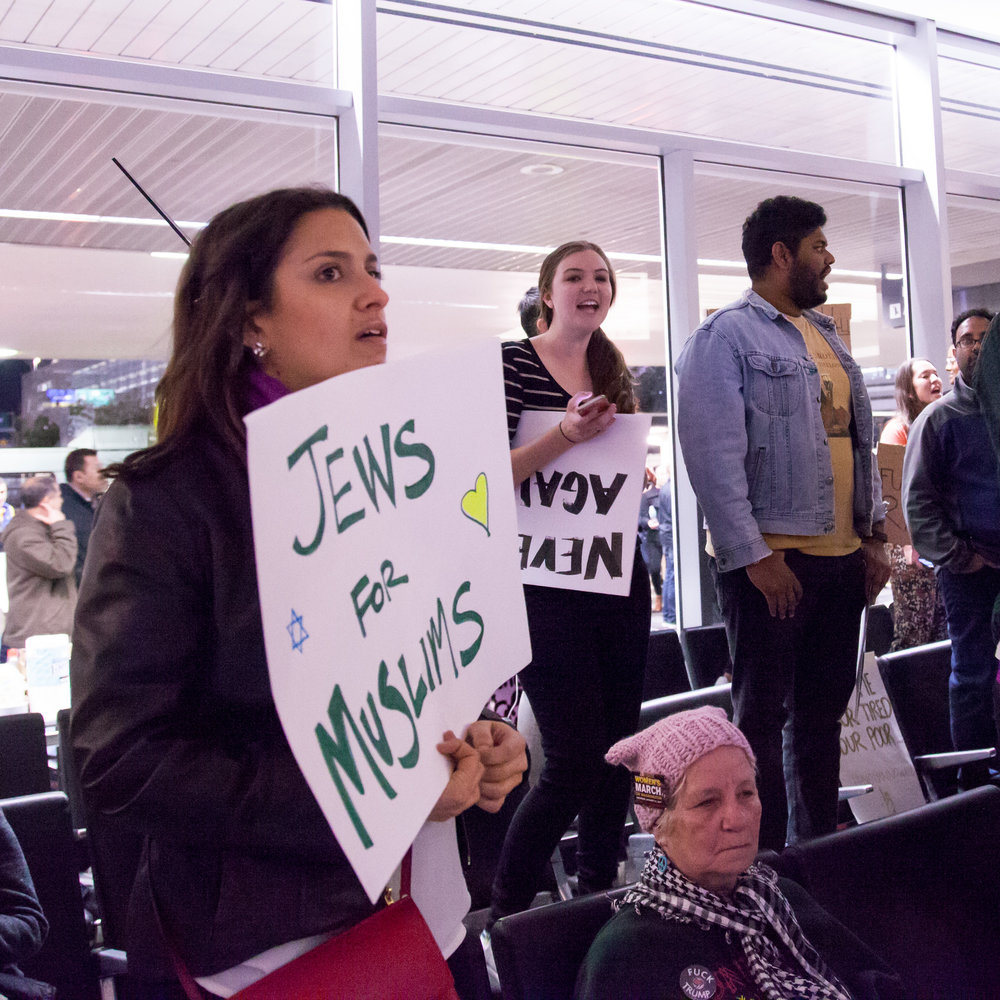 "At left, a protester at San Francisco International Airport holds a sign reading ""Jews For Muslims"" during a demonstration against the Trump administration's temporary travel ban affecting Muslim-majority countries Jan. 29, 2017. Credit: Kenneth Lu via Wikimedia Commons."