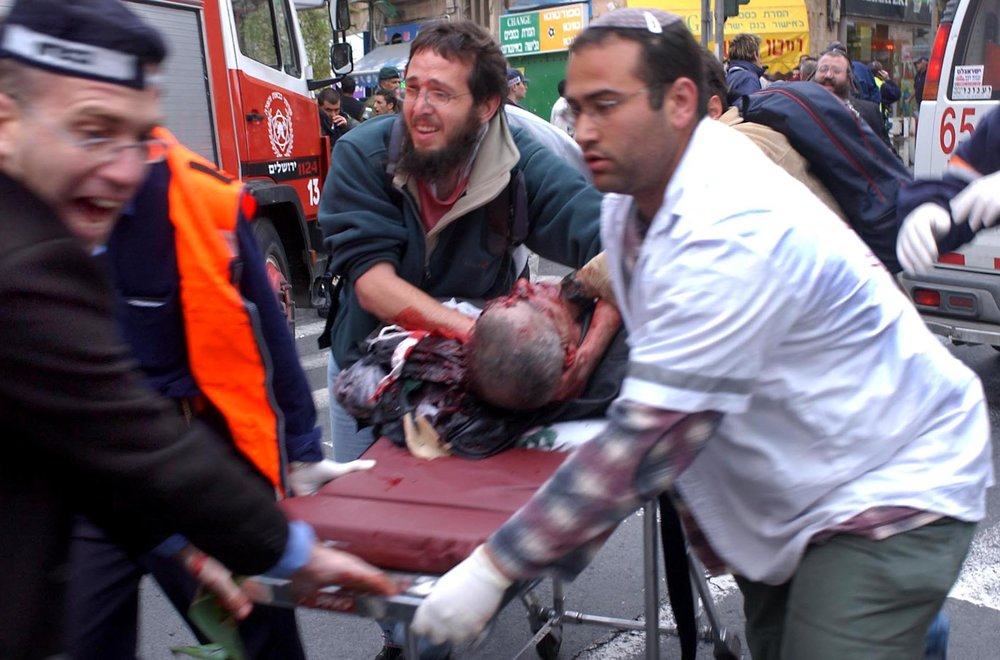 Medics help a man wounded in the Aug. 9, 2001, bombing of the Sbarro pizza restaurant in downtown Jerusalem, which killed 15 people, including seven children and a pregnant women, and wounded 130 others.Credit: Yossi Zamir/Flash90.