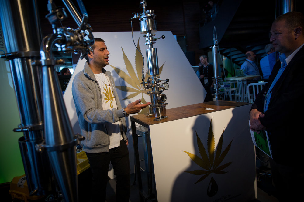 At the annual CannaTech medical marijuana innovation conference in Tel Aviv March 20, an exhibitor gives a presentation about creating high-concentrate oils with a cannabis extraction machine. Credit: Miriam Alster/Flash90.